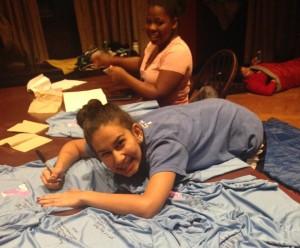 Pratiksha Mishra signing shirts and Tanayshia Johnson finishing Algebra homework
