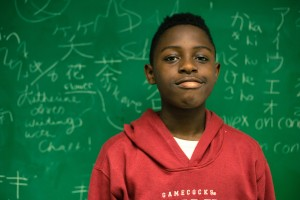 hucktown Squash student J'Mari Butler in front of a College of Charleston classroom's chalkboard